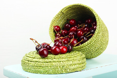 Fresh cherries in basket on white wall background photo