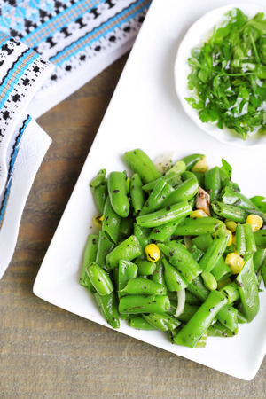 Salad with green beans and corn with sauce on plate , on color wooden background photo