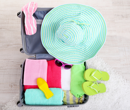 Suitcase with things on white carpet on the floor for travelling somewhere close to water for spending summer vacation photo