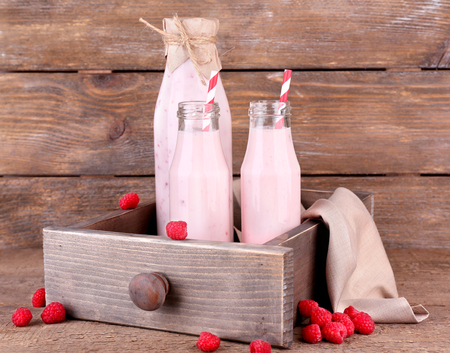 Bottles of tasty raspberry smoothie drinks on grey pink wooden background photo