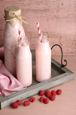 Bottles of tasty raspberry smoothie drinks on pink wooden background photo