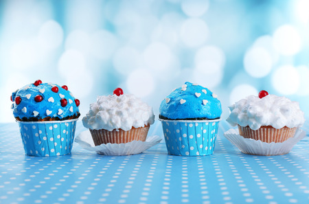 Tasty cupcakes on table, on bright background photo