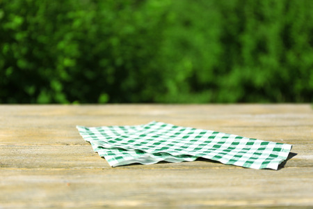 Wooden table with tablecloth, outdoors  photo