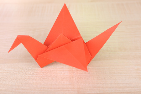 Origami crane on wooden table photo