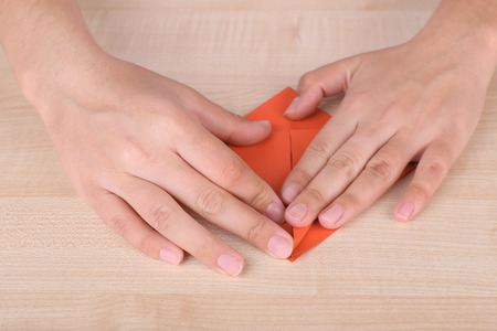 Hands making origami figure, close up photo