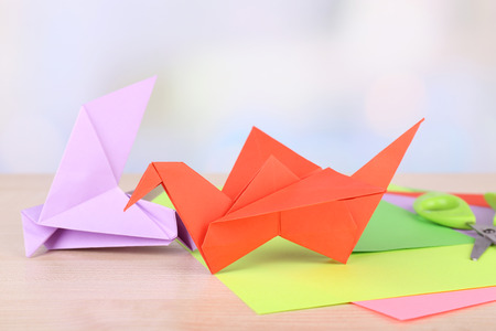 Origami crane and paper on wooden table photo