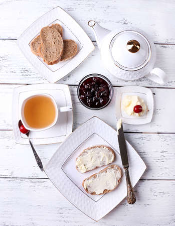 Fresh bread with cherry jam and homemade butter on plate on wooden background photo
