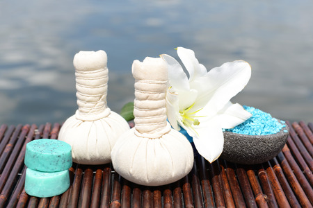 Herbal remedies for massage on bamboo mat, outdoor  photo