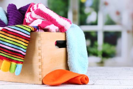 Chaussettes multicolores dans la boîte sur une table en bois en face de la fenêtre Banque d'images