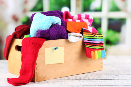dirty clothes: Multicoloured socks in box on a wooden table in front of the window Stock Photo