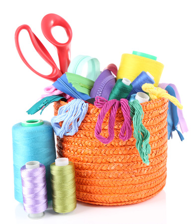 necessary: Round orange box full of multicoloured threads and everything necessary for sewing on white background isolated