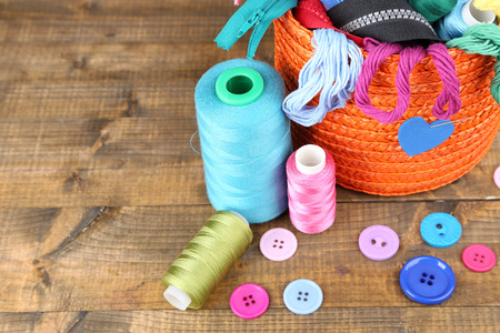 necessary: Round orange box full of multicoloured thread and everything necessary for sewing on wooden background Stock Photo