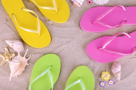 Bright flip-flops on sand, close up photo