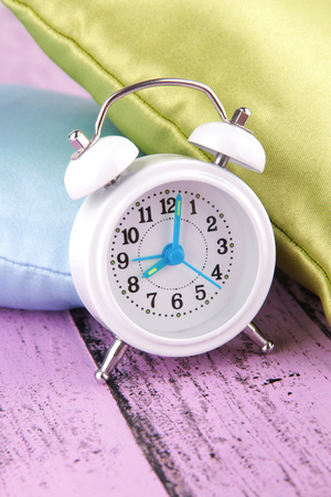 Plastic clock on a silk pillows on wooden background photo