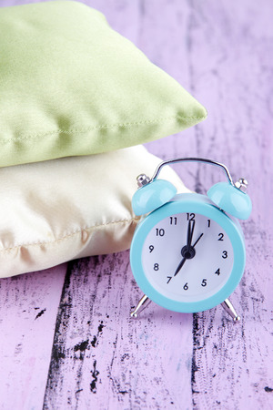 Plastic clock on a silk pillows on wooden purple background photo