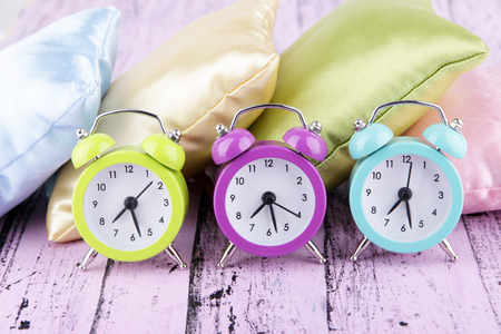 Plastic clocks on a silk pillows on wooden background photo