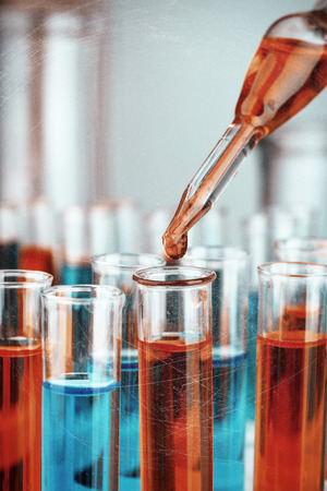 Laboratory pipette with drop of color liquid over glass test tubes, close up photo