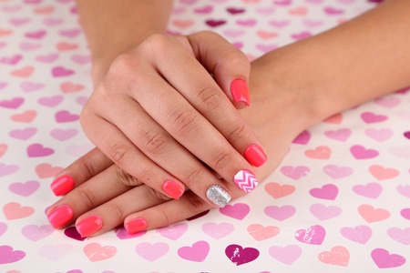 Female hand with stylish colorful nails, on bright background photo