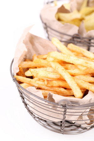 Tasty french fries in metal basket and potato chips, isolated on white photo