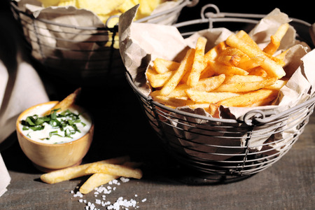 Tasty french fries in metal basket and potato chips on wooden table with dark light  photo