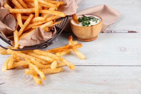 Tasty french fries in metal basket on wooden table photo