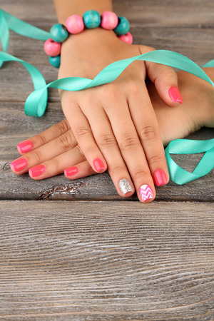 Female hand with stylish colorful nails, on wooden background