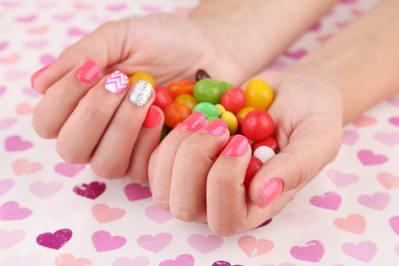 Female hand with stylish colorful nails holding colorful candies, on bright background photo