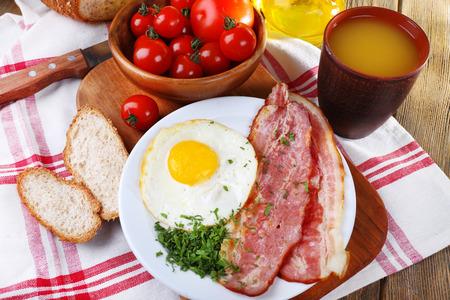huevos revueltos: Huevos revueltos con tocino y verduras servido en un plato en la servilleta