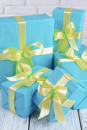 Beautiful gifts on table on brick wall background photo