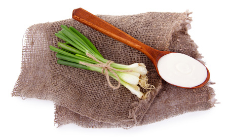 tuft: Wooden spoon of cream and a tuft of onion on piece of sacking on white background isolated