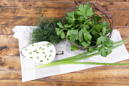 tuft: Metal bowl of cream with a tuft of onion, dill and parsley in a basket near it on a napkin on wooden background Stock Photo