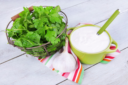 tuft: Green pan of cream and a tuft of dill and garlic on a napkin on wooden background