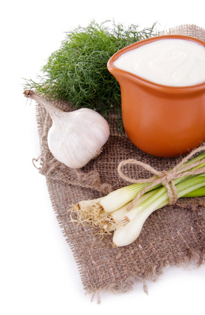 tuft: Clay pot with cream and a tuft of onion, dill and garlic near it on a piece of sacking on white background isolated