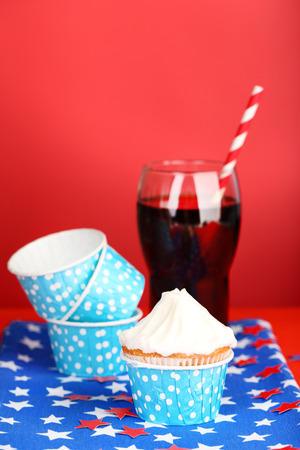 American patriotic holiday cupcake and glass of cola on red background photo
