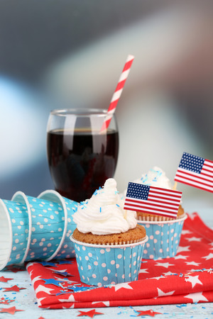 American patriotic holiday cupcakes and glass of cola on wooden table photo