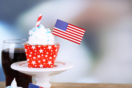 American patriotic holiday cupcake and glass of cola on wooden table photo
