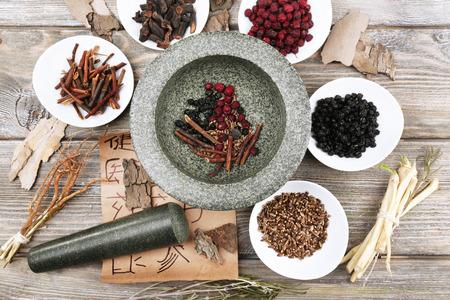 medicina tradicional china: Tradicionales ingredientes de hierbas medicinales chinas con jeroglíficos no reales, de cerca Foto de archivo