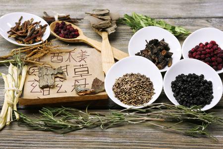 Tradicionales ingredientes de hierbas medicinales chinas con jeroglíficos no reales, de cerca Foto de archivo