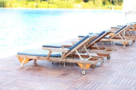 Lounge sunbeds near swimming pool photo