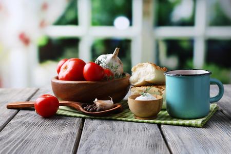 Jugo de tomate hecha en casa en taza del color, palitos de pan, especias y tomates frescos en mesa de madera, en brillante