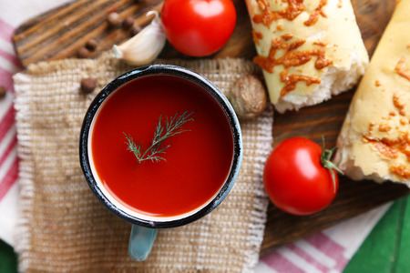 Homemade tomato juice in mug, spices and fresh tomatoes on wooden background photo