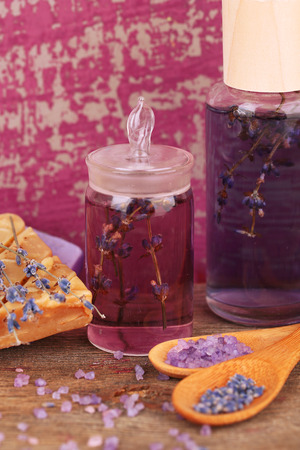 Spa still life with lavender oil and flowers on wooden table Stock Photo