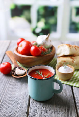 Homemade tomato juice in color mug, bread sticks, spices and fresh tomatoes on wooden table, on bright photo