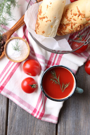Homemade tomato juice in color mug, bread sticks, spices and fresh tomatoes on wooden background photo