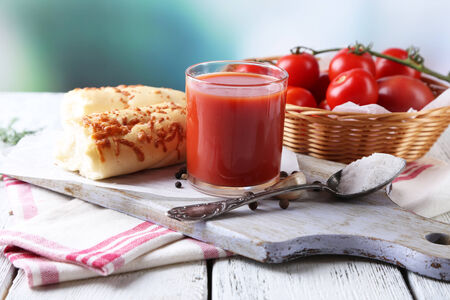 Homemade tomato juice in glass, spices and fresh tomatoes on wooden background photo