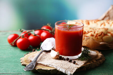 Homemade tomato juice in glass, spices and fresh tomatoes on wooden  table, on bright background photo