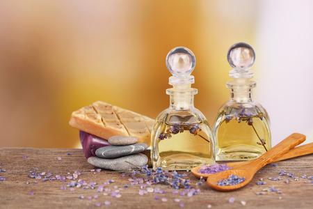 Spa stilleven met lavendelolie en bloemen op houten tafel, op lichte achtergrond