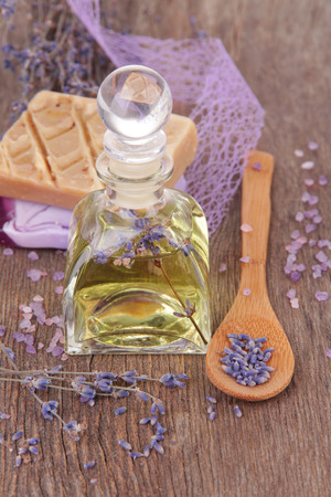 Spa still life with lavender oil and flowers on wooden table photo