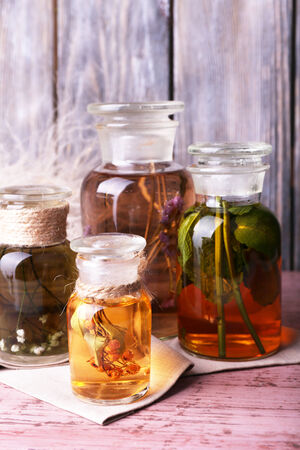 tincture: Bottles of herbal tincture on a napkin on  wooden table in front of wooden wall