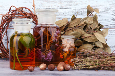 tincture: Bottles of herbal tincture and dried leaves on wooden background